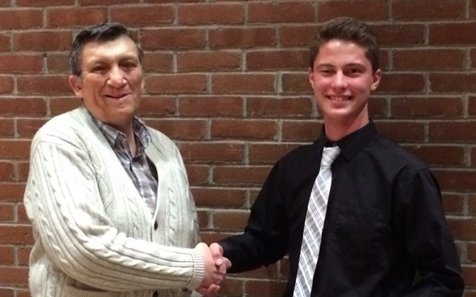 Manistique High School Senior, Logan Kraatz, is congratulated by Larry Peterson of the Schoolcraft County Historical Society. Logan won 1st place in the recent essay contest and received an award of $350. He will attend the University of Michigan in the fall.