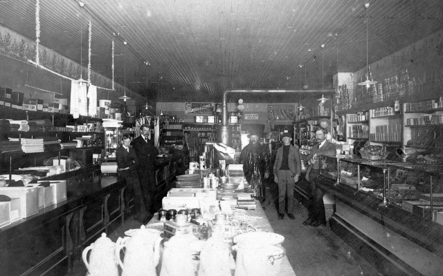 "Interior of the Middlebrook Grocery located on Manistique's Westside. The stock included a mixture of grocery, dry goods and hardware items. The shelves were lined with canned goods and signs in the rear of the store advertised ""Mexoja"" high grade coffee and Oleo margarine"