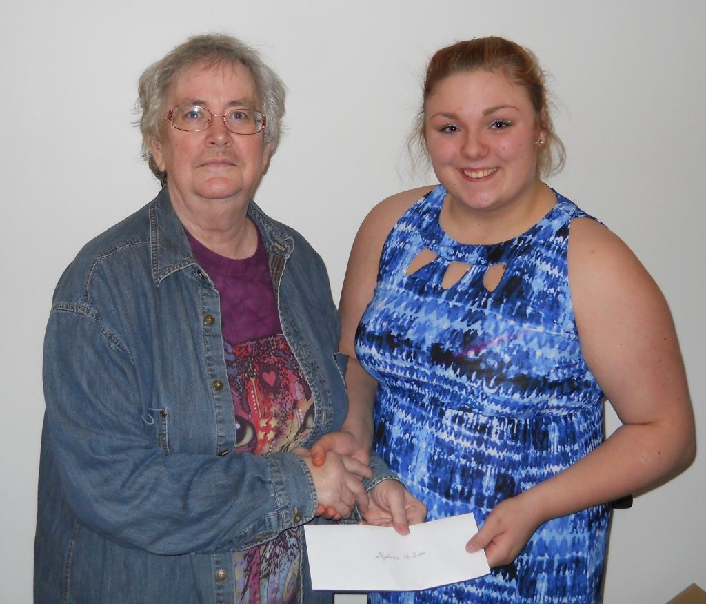 "Manistique High School Junior Stephanie LaFoille receives her 2nd Prize award of $150.00 from Rebecca Peterson of the Schoolcraft County Historical Society for her essay ""Businesses in Schoolcraft County."""
