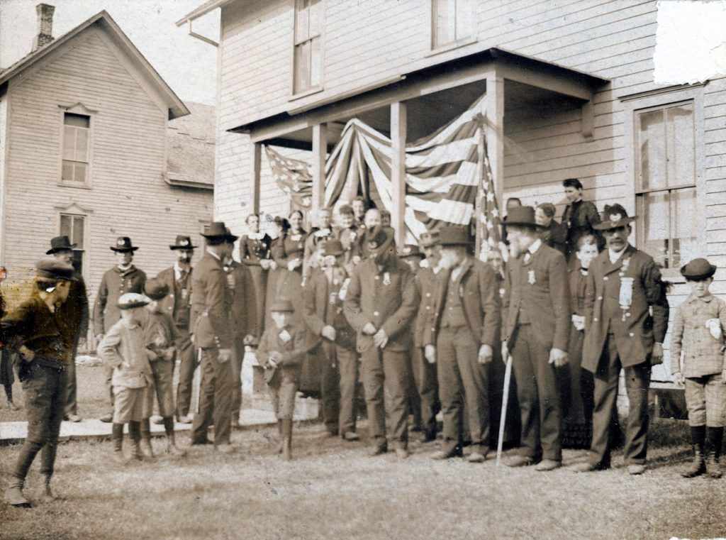 The above is a rare photo of Manistique's Civil War veterans getting ready for a patriotic holiday celebration. Pictured from far right: John Gayar, Henry Brassel, Amos Hill, George W. Rice  (partially hidden behind Hill) and Wright E. Clarke (buttoning coat), On the far left, the men with insignias on their hats are David Blair (left) and William Wood (Right).